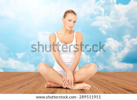 wellness, health and people concept - beautiful young woman in cotton underwear sitting on wooden floor over white clouds and blue sky background - stock photo