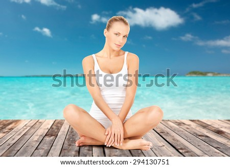wellness, health and people concept - beautiful young woman in cotton underwear sitting on wooden floor over sea and blue sky background - stock photo