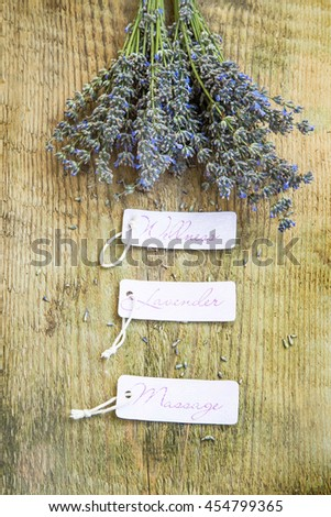 Wellness lavender massage labels with lavender bunch flowers on rustic wooden background - stock photo