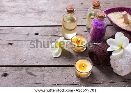 Wellness or spa  setting. Bottles with aroma oil, sea salt, towels  and  white  plumeria on vintage wooden background. Selective focus. Place for text. - stock photo