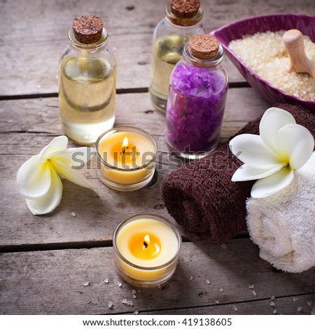 Wellness or spa  setting. Bottles with aroma oil, sea salt, towels  and  white  plumeria on vintage wooden background. Selective focus. Square image. - stock photo