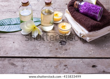 Wellness or spa  setting. Bottles with aroma oil, sea salt, towels  on vintage wooden background. Selective focus. Place for text. - stock photo