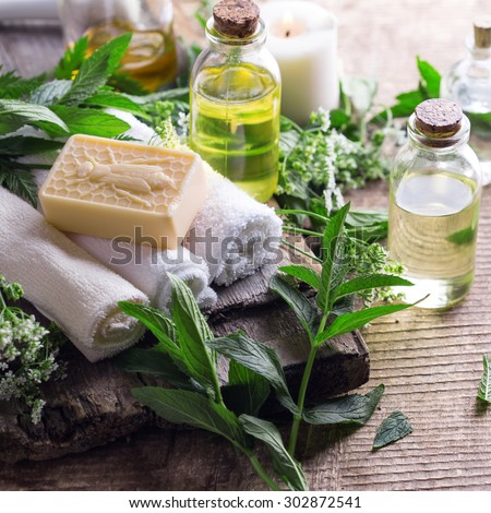 Wellness setting. Essential aroma oil, towels, soap on aged  wooden background. Selective focus. Square image. - stock photo