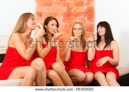 Wellness - young, happy female friends drinking champagne in spa and have fun - stock photo