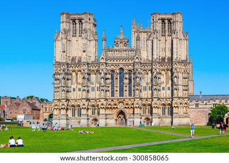 WELLS, ENGLAND - JUNE 30, 2015: Wells Cathedral with unidentified people is a Church of England in Wells, Somerset, dedicated to St Andrew the Apostle, and is the seat of the Bishop of Bath and Wells - stock photo