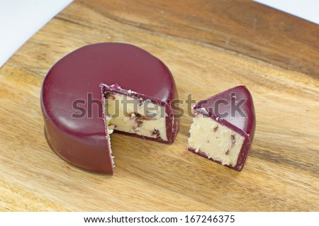 Wensleydale and Cranberry in red wax on wooden board - stock photo