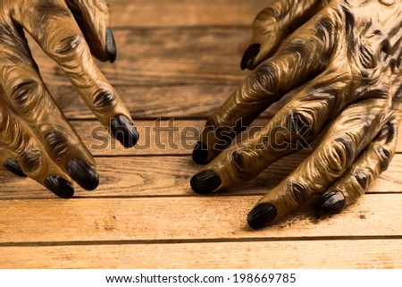 Werewolf or zombie hands resting on rustic wooden table for Halloween - stock photo