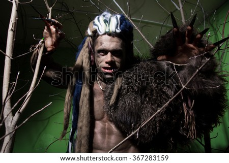 Werewolf with long nails and crooked teeth among the branches of the tree. Gothic image of scary diabolical creatures for Halloween - stock photo