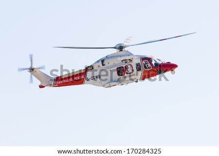 WEST BAY, UK - JULY 27, 2008: A UK Coastguard Helicopter in mid-air during a rescue operation on the Dorset coastline near West Bay, England on 27th July 2008.