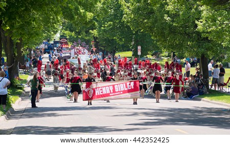 WEST ST. PAUL, MINNESOTA - MAY 21, 2016: Henry Sibley High School marching band proceeds up Smith Avenue during Grande Parade in West St. Paul on May 21.  - stock photo