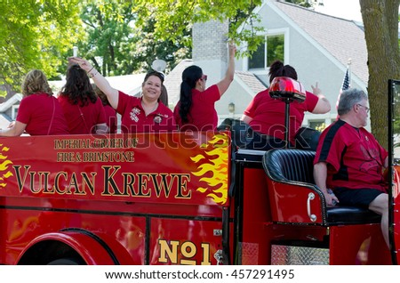 WEST ST. PAUL, MINNESOTA - MAY 21, 2016: Lady Ferty and Vulcan Krewe of Saint Paul Winter Carnival lore in red fire truck wave to crowd during annual West St. Paul Days Grande Parade on May 21.  - stock photo