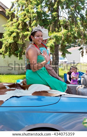 WEST ST. PAUL, MINNESOTA - MAY 21, 2016: Princess and Prince of West Wind for St. Paul Winter Carnival Alyssa Ortiz and Scott Oien wave to crowd at Grande Parade in West St. Paul on May 21.  - stock photo