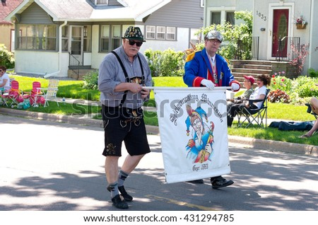 WEST ST. PAUL, MINNESOTA - MAY 21, 2016: Two members of German Karneval Club or Spielmannszug of Minnesota march with banner during annual West St. Paul Days Grande Parade on May 21.  - stock photo