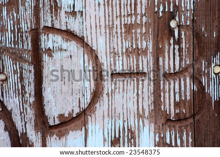 "Western branding iron brand marks, ""D"" and ""B"" burned into a vintage wooden door through fading turquoise paint. - stock photo"