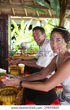 Western couple getting married during a traditional Buddhist wedding in Thailand. - stock photo