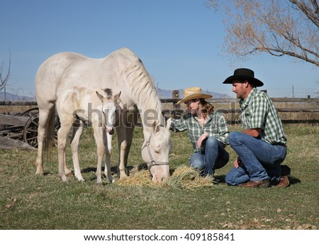 western couple with mother horse and baby foal in a field - stock photo