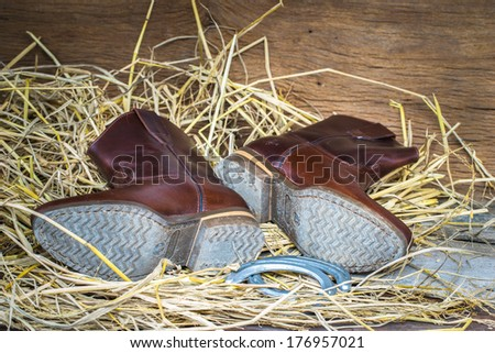 Western cowboy boots and horseshoes ,Still life vintage style - stock photo
