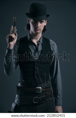 Western 1900 fashion man with brown hair and hat holding gun. Studio shot against grey.