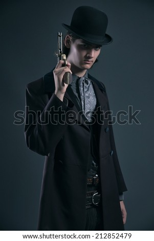 Western 1900 fashion man with brown hair and hat holding gun. Studio shot against grey. - stock photo