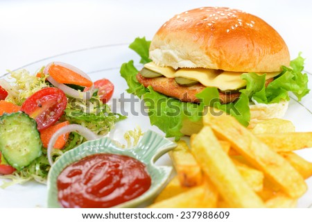 Western fast food (focus on burger, foreground blurred) - stock photo