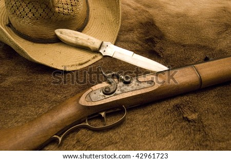 Western Gear Showing a hat, knife and a old rifle on top of a deer skin - stock photo