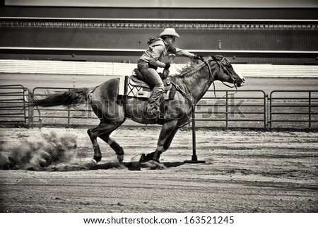 Western horse and rider competing in pole bending and barrel racing competition. Gritty look with sepia toning. - stock photo
