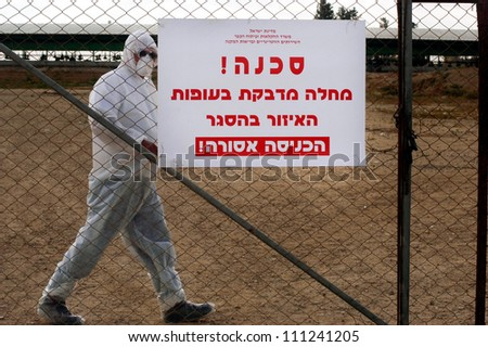 """WESTERN NEGEV, ISRAEL - MARCH 17: Poultry farmer inside his turkey farm during bird flu outbreak near a warning sign in Hebrew: """"Contagious Bird Flu"""" on March 17, 2006  in kibbutz Ein Hashlosha,Israel. - stock photo"""