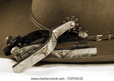 Western or cowboy themed image of a cowboy hat and fancy spurs on a white surface (sepia tint added) - stock photo