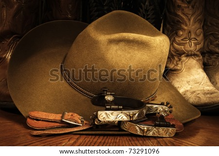 Western or cowboy themed image of a cowboy hat, fancy spurs, spur leathers and cowboy boots arranged on a wood grained surface with lighting accents. - stock photo