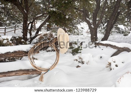 Western ranching equipment including a lasso and cowboy hat on a fence in the thick winter snow. - stock photo