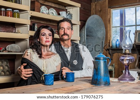 Western sheriff poses with a woman for a portrait inside a house - stock photo