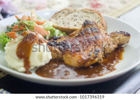 western style food contains baked chicken, potato mashed, salad, bread and some gravy serve on plate