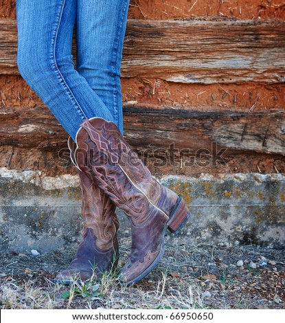 Western style image of cowgirl's legs in jeans and boots on deserted wall background - stock photo