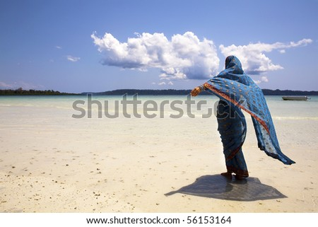 Western woman in saree enjoys the breeze while looking out across the ocean. Andaman islands, India