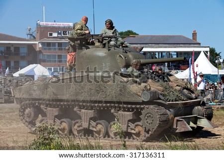 WESTERNHANGER, UK - JULY 19: A WW2 Sherman tank leaves the main arena having just participated in a battle re-enactment for the public at the War & Peace show on July 19, 2013 in Westernhanger