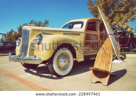 WESTLAKE, TEXAS - OCTOBER 18, 2014: A yellow 1941 Packard 110, wood bodied station wagon, is on display at the 4th Annual Westlake Classic Car Show. Front side view. Vintage style effects. - stock photo
