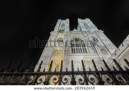 Westminster Abbey cathedral from below with dramatic sky, light post and fence, night shoot, London, United Kingdom - stock photo