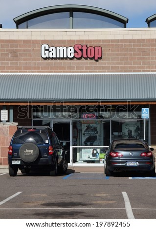 WESTMINSTER, COLORADO/U.S.A. - APRIL 15, 2012:  Game Stop retail store with customer vehicles in the parking lot.  The entrance door to Game Stop, with the Game Stop sign above.