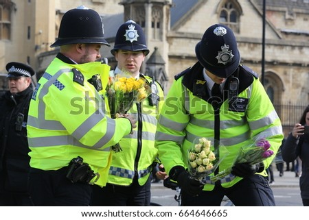 Westminster, London. March 24, 2017. Policemen in London lay flowers from the public in memory of victims of the London bridge attack. One of their colleagues, Keith Palmer, died in the terror attack