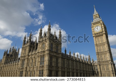 Westminster Palace and Big Ben shine under a mix of morning London sun and clouds - stock photo