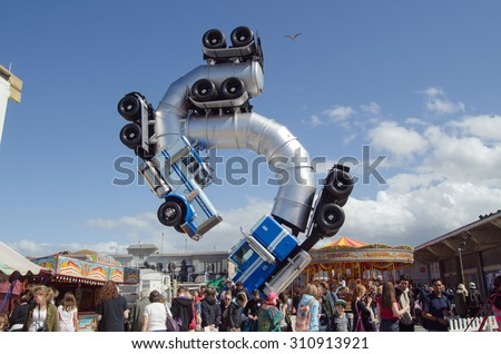 WESTON-SUPER-MARE, UK - AUGUST 26, 2015:  A seagull flies over the top of the truck ballet sculpture by Mike Ross at the Banksy inspired Dismaland theme park parody in Weston-Super-Mare, Somerset.  - stock photo