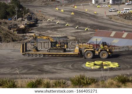 WESTPORT, NEW ZEALAND, AUGUST 31, 2013: a 40 ton digger hitches a ride on a huge custom-built transporter at an open cast coal mine on August 31, 2013 near Westport, New Zealand - stock photo