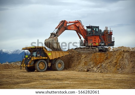 WESTPORT, NEW ZEALAND, JULY 12, 2013: A 190 ton digger loads a 130 ton truck with rock overburden at Stockton open cast coal mine on July 12, 2013 near Westport, New Zealand.