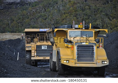 WESTPORT, NEW ZEALAND, JULY 20, 2009: Huge trucks move high grade coal from a stockpile at the Stockton Coal Mine near Westport, New Zealand - stock photo