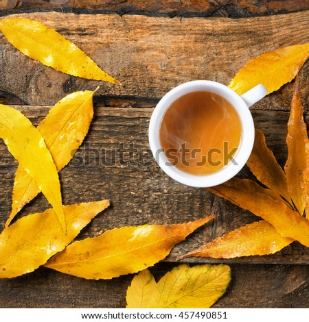 Wet autumn yellow leaves and cup of hot tea on old weathered wood in rainy weather. Top view point.