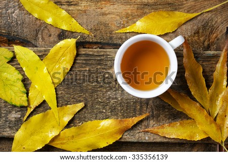 Wet autumn yellow leaves and cup of tea on old weathered wood in rainy weather. Top view point. - stock photo