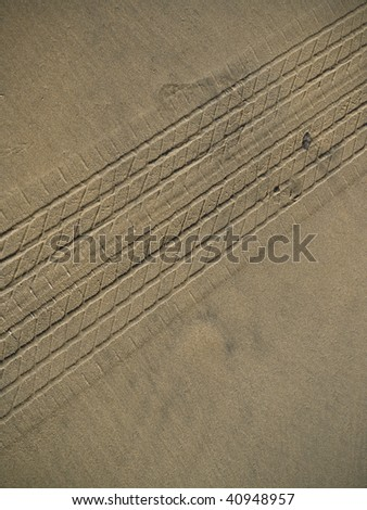 wet beach sand with car tire tracks in it. - stock photo