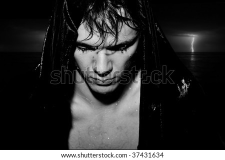 Wet beautiful man. Studio shot. Black background - stock photo