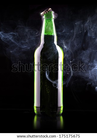 wet Beer bottle with chill smoke on a black