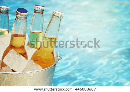 Wet bottle of beer on watter pool in the summer day - stock photo